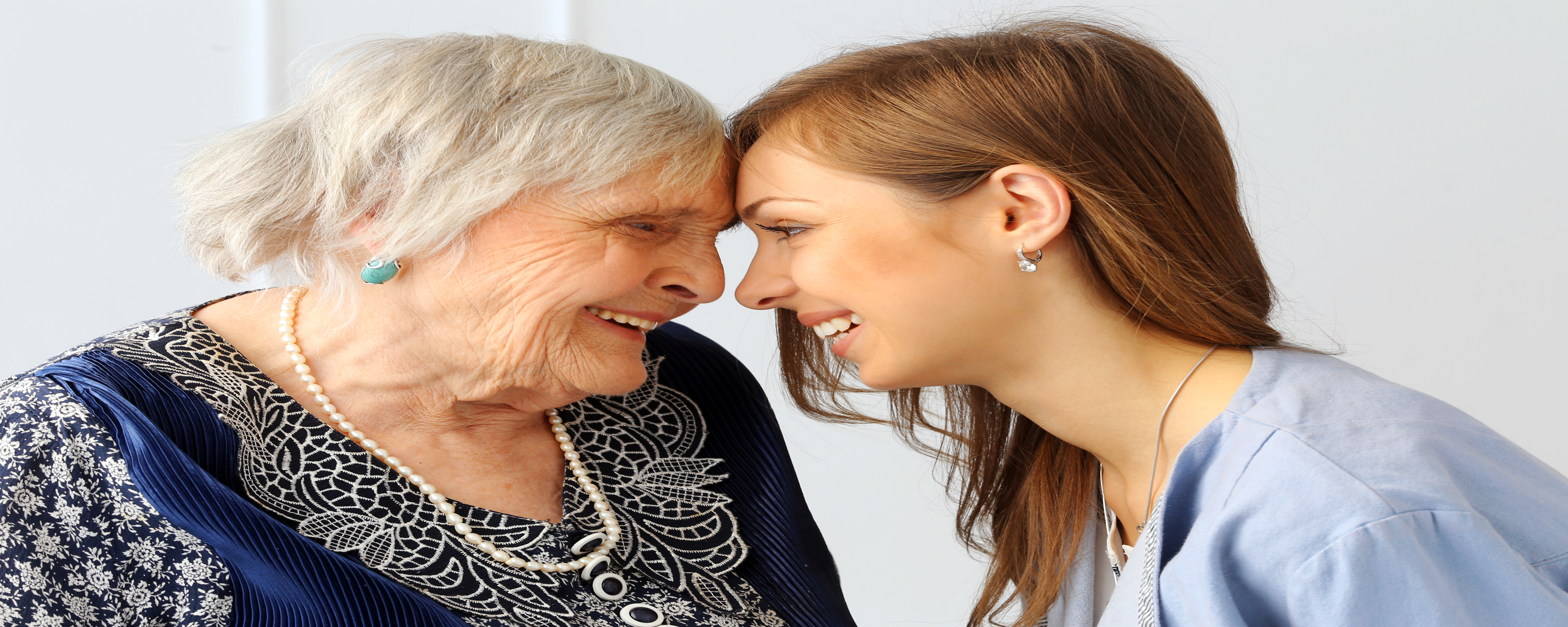 Aging adult and young person lovingly looking at each other