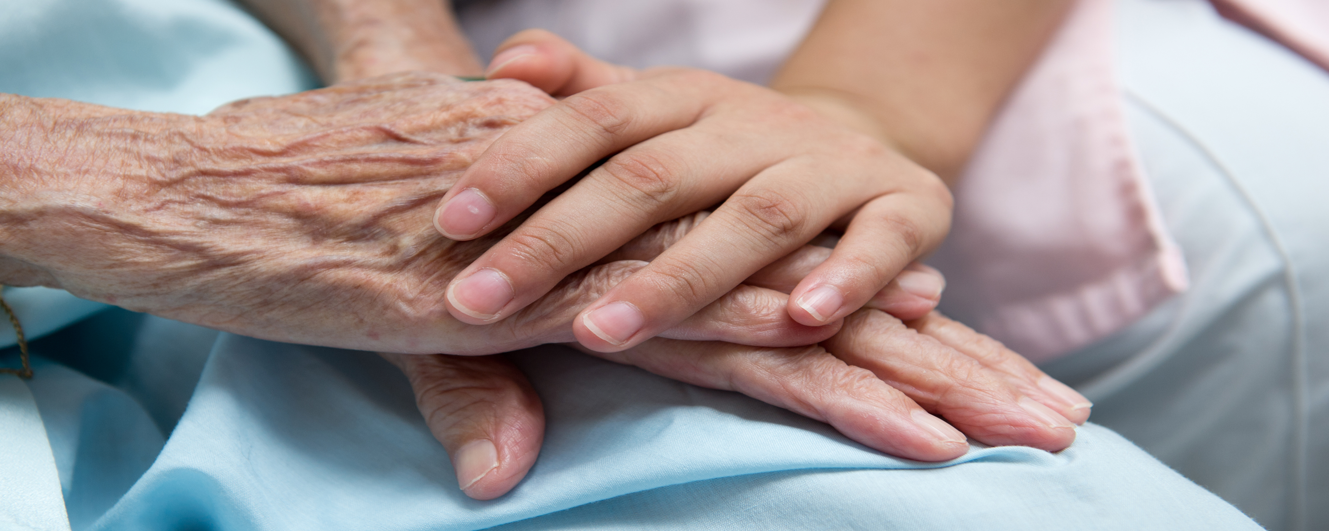 Aging adult and younger person holding hands